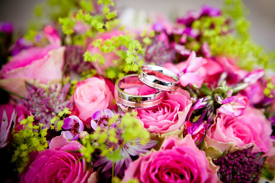 wedding rings on top of a bouquet