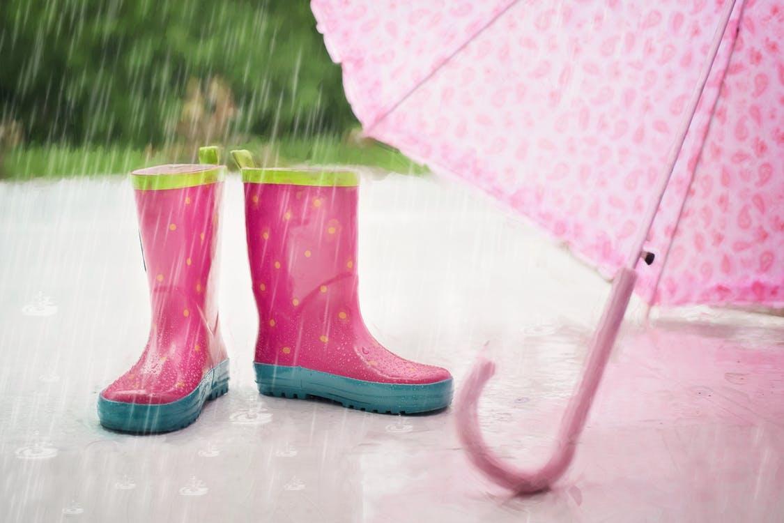 Kids boots and umbrella in the rain