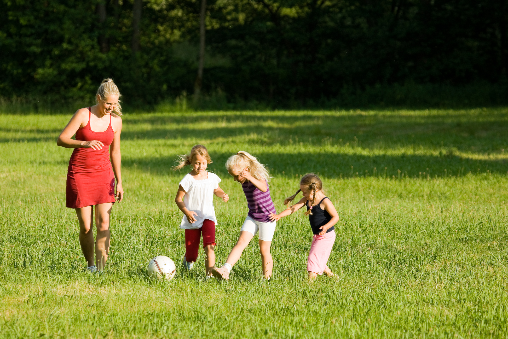 a mom and her three kids playing in the field